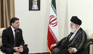 **FILE** Syrian Prime Minister Wael Nader al-Halqi (left) talks Aug. 31, 2012, with Iranian supreme leader Ayatollah Ali Khamenei, under a portrait of Iranian late revolutionary founder Ayatollah Khomeini, during their meeting in Tehran. (Associated Press/Office of the Iranian Supreme Leader)
