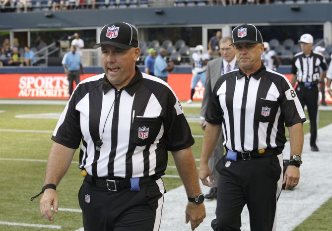 FILE - This Aug. 11, 2012 file photo shows replacement officials taking the field at the start of an NFL football preseason game between the Seattle Seahawks and the Tennessee Titans, in Seattle. The NFL will open the regular season with replacement officials. League executive Ray Anderson has told the 32 teams that with negotiations remaining at a standstill between the NFL and the officials' union. The replacements will be on the field beginning next Wednesday night, Sept. 5, 2012,  when the Cowboys visit the Giants to open the season. (AP Photo/Rick Bowmer, File)