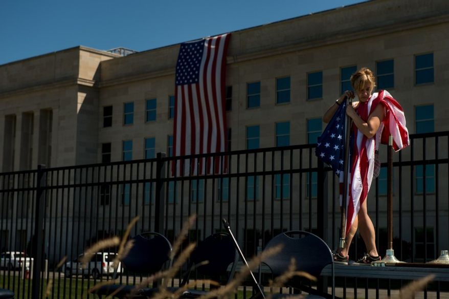 Misty (who declined to give her last name) with Electrum Productions takes down an American flag after a morning ceremony at the Pentagon 9/11 Memorial, Arlington, Va., Tuesday, Sept. 11, 2012. (Andrew Harnik/The Washington Times)