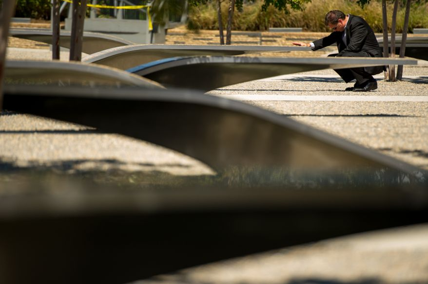 Duffy Newman of Sterling, Va., visits the bench of Barbara Edwards, his best friend's mother who he was very close with, on the 11th anniversary of 9/11 at the Pentagon 9/11 Memorial, Arlington, Va., Tuesday, Sept. 11, 2012. (Andrew Harnik/The Washington Times)