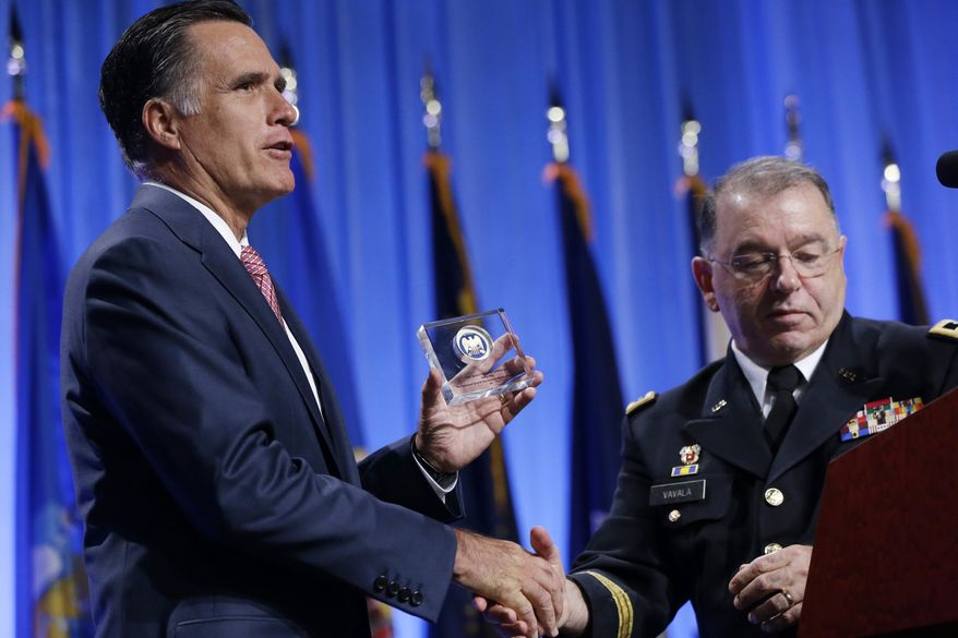 Republican presidential candidate Mitt Romney receives a commemorative coin from Maj. Gen. Francis D. Vavala after he addressed the National Guard Association Convention in Reno, Nev., on Sept. 11, 2012. (Associated Press)