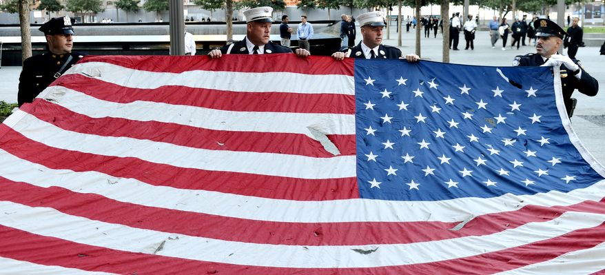 Police officers of the Port Authority of New York and New Jersey carry an American flag that flew over at the World Trade Center towers on Sept. 11, 2012, during a ceremony for the 11th anniversary of 9/11 at the site of the World Trade Center in New York. (Associated Press)
