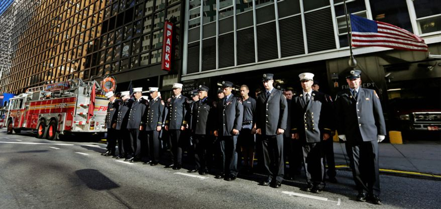 Firefighters from New York's Engine 8 and Ladder 2 stand on East 51st Street in front of their firehouse during a ceremony honoring fallen FDNY firefighters and victims on the 11th anniversary of the Sept. 11, 2001, terrorist attacks. Ten members of the station died in the attack. (AP Photo/Charles Krupa)