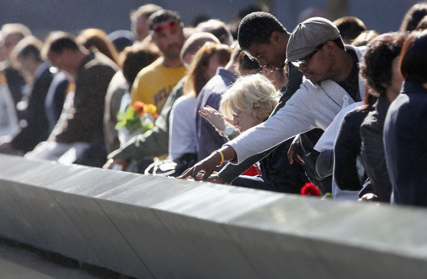 ** FILE ** Family members view the names of their relatives etched into the 9/11 Memorial during the commemoration of the 11th anniversary of the terrorist attacks on the World Trade Center. (AP Photo/John Moore, Pool)