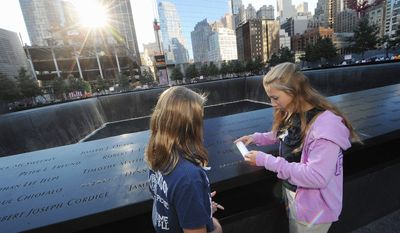 Shannon and Lauren Gullickson scratch the name of their uncle, Firefighter Joe Gullickson, on paper as friends and relatives of the victims of the Sept. 11 terrorist attacks on the World Trade Center attend a ceremony marking the 11th anniversary of the attacks at the National Sept. 11 Memorial at the World Trade Center site. (AP Photo/The Daily News, Todd Maisel, Pool)
