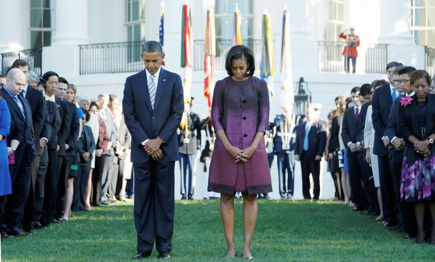 President Obama and first lady Michelle Obama, joined by members of the White House staff, pause during a moment of silence to mark the 11th anniversary of 9/11, on Tuesday, Sept. 11, 2012, on the South Lawn of the White House in Washington. (AP Photo/Carolyn Kaster)