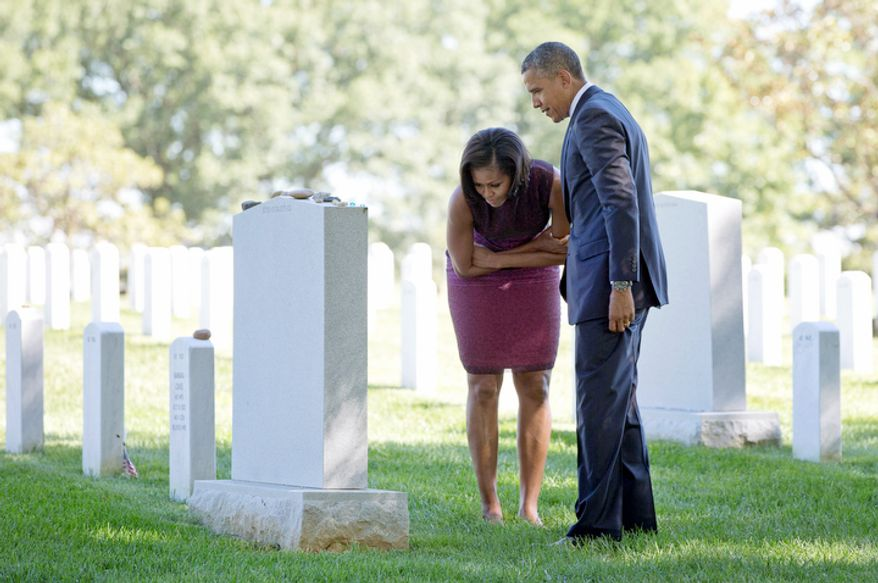 President Obama and first lady Michelle Obama visit Section 60 of Arlington National Cemetery and place Challenge Coins on tombstones on Tuesday, Sept. 11, 2012. (AP Photo/Carolyn Kaster)
