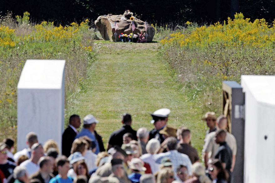 A boulder (top center) that represents the final resting place for the 40 passengers and crew of Flight 93 is viewed by visitors to the Flight 93 National Memorial after a memorial service in Shanksville, Pa., on Tuesday, Sept. 11, 2012. (AP Photo/Gene J. Puskar)