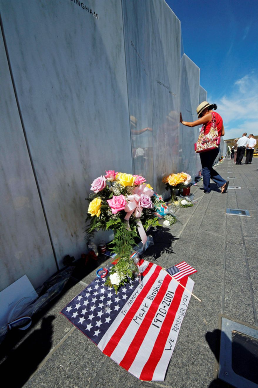 A visitor to the Flight 93 National Memorial pauses at the Wall of Names, containing the names of the 40 passengers and crew who died in the crash of United Flight 93, on Tuesday, Sept. 11, 2012, following a memorial service in Shanksville, Pa. (AP Photo/Gene J. Puskar)