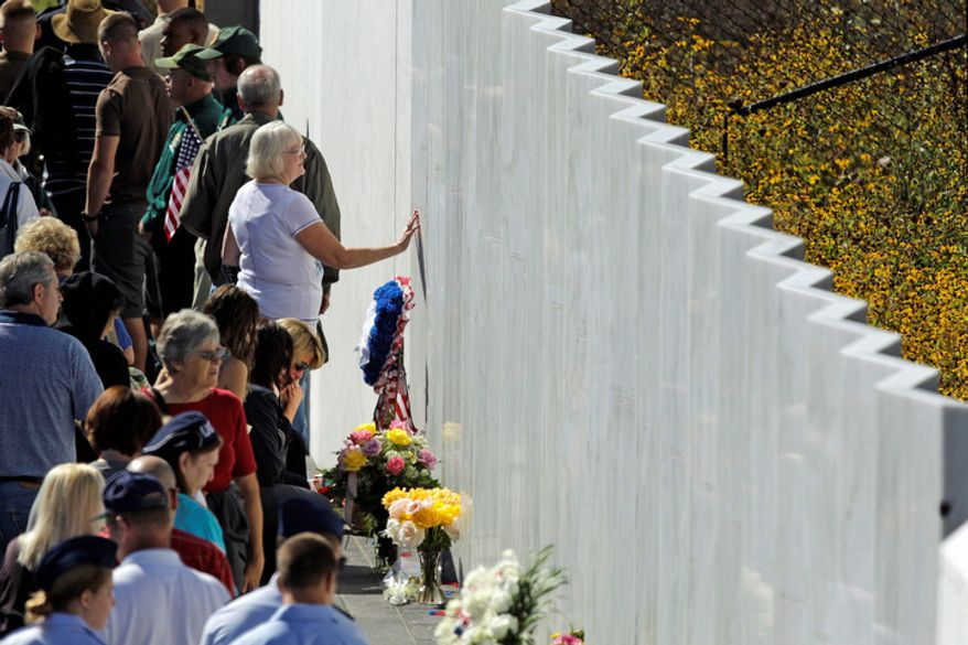 Visitors to the Flight 93 National Memorial pause at the Wall of Names, containing the names of the 40 passengers and crew who died in the crash of United Flight 93, following a memorial service in Shanksville, Pa., on Tuesday, Sept. 11, 2012. (AP Photo/Gene J. Puskar)
