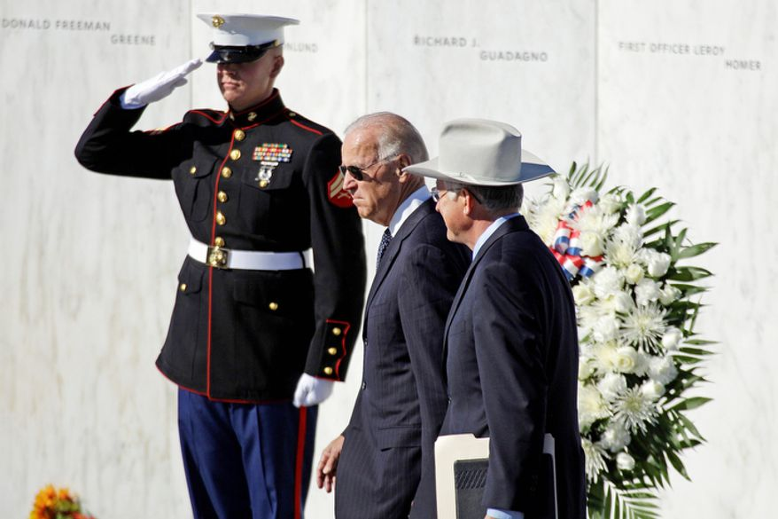Vice President Joseph R. Biden (center) and Interior Secretary Ken Salazar (right) walk in front of the Wall of Names, containing the names of the 40 passengers and crew of Flight 93, as they arrive for a memorial service at the Flight 93 National Memorial in Shanksville, Pa., on Tuesday, Sept. 11, 2012. (AP Photo/Gene J. Puskar)