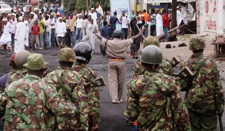 """Kenyan paramilitary soldiers move forward to disperse Muslim youths outside the Musa Mosque in Mombasa, days after the Aug. 27 killing of Aboud Rogo Mohammed, a Muslim preacher accused of links to a terrorist group in Somalia. """"Extremism divides people as 'we versus them' and that brings tension,"""" said the Rev. Wilybard Lagho, a Catholic priest who is chairman of an interfaith group of clerics in Mombasa which gathers to discuss their common concerns. (Associated Press)"""