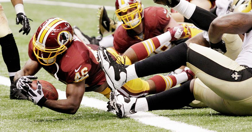 Redskins rookie running back Alfred Morris, shown scoring one of his two touchdowns, says he has to be ready for a handoff at all times from fellow rookie Robert Griffin III when Washington utilizes its zone-read running scheme. Morris ran six times for 16 yards out of the formation Sunday. (Associated Press)