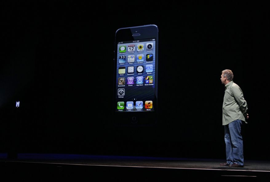 **FILE** Phil Schiller, Apple's senior vice president of worldwide marketing, watches on stage Sept. 12, 2012, the unveiling of the new iPhone 5 at an Apple event in San Francisco. (Associated Press)