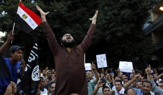 "Egyptian protesters carry their national flag and a flag with Arabic that reads ""No God but Allah, and Mohammed is his prophet,"" and chant anti-U.S. slogans during a demonstration in front of the U.S. Embassy in Cairo on Sept. 12, 2012, as part of widespread anger across the Muslim world about a film ridiculing Islam's prophet Muhammad. (Associated Press)"