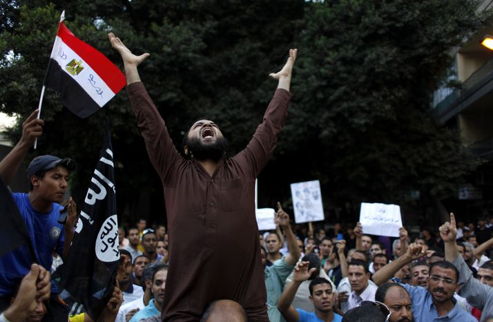 """Egyptian protesters carry their national flag and a flag with Arabic that reads """"No God but Allah, and Mohammed is his prophet,"""" and chant anti-U.S. slogans during a demonstration in front of the U.S. Embassy in Cairo on Sept. 12, 2012, as part of widespread anger across the Muslim world about a film ridiculing Islam's prophet Muhammad. (Associated Press)"""