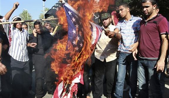 "**FILE** Palestinians burn a U.S. flag during a protest against the movie, ""Innocence of Muslims,"" near the United Nations office in Gaza City, Wednesday, Sept. 12, 2012. Muslim anger over perceived Western insults to Islam has exploded several times, most recently in Tuesday's attacks against U.S. diplomatic posts in the Middle East in which U.S. ambassador to Libya Chris Stevens and three other Americans were killed. (AP Photo/Adel Hana)"