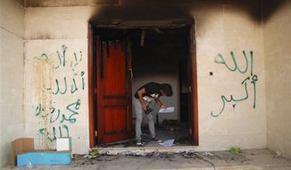"A man looks at documents at the U.S. consulate in Benghazi, Libya, after an attack that killed four Americans, including Ambassador Chris Stevens, Wednesday, Sept. 12, 2012. The graffiti reads, ""no God but God,"" ""God is great,"" and ""Muhammad is the Prophet."" The American ambassador to Libya and three other Americans were killed when a mob of protesters and gunmen overwhelmed the U.S. Consulate in Benghazi, setting fire to it in outrage over a film that ridicules Islam's Prophet Muhammad. (AP Photo/Ibrahim Alaguri)"