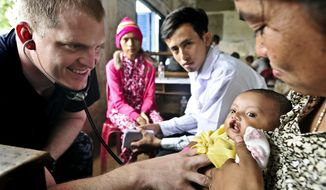 U.S. Navy Lt. Thom Miller (left) listens to the heartbeat of a baby girl at the Hun Sen Cheungkor Primary School near Sihanoukville, Cambodia, on Tuesday, July 31, 2012, during a visit to the country by the hospital ship USNS Mercy. (AP Photo/U.S. Navy, Kristopher Radder)