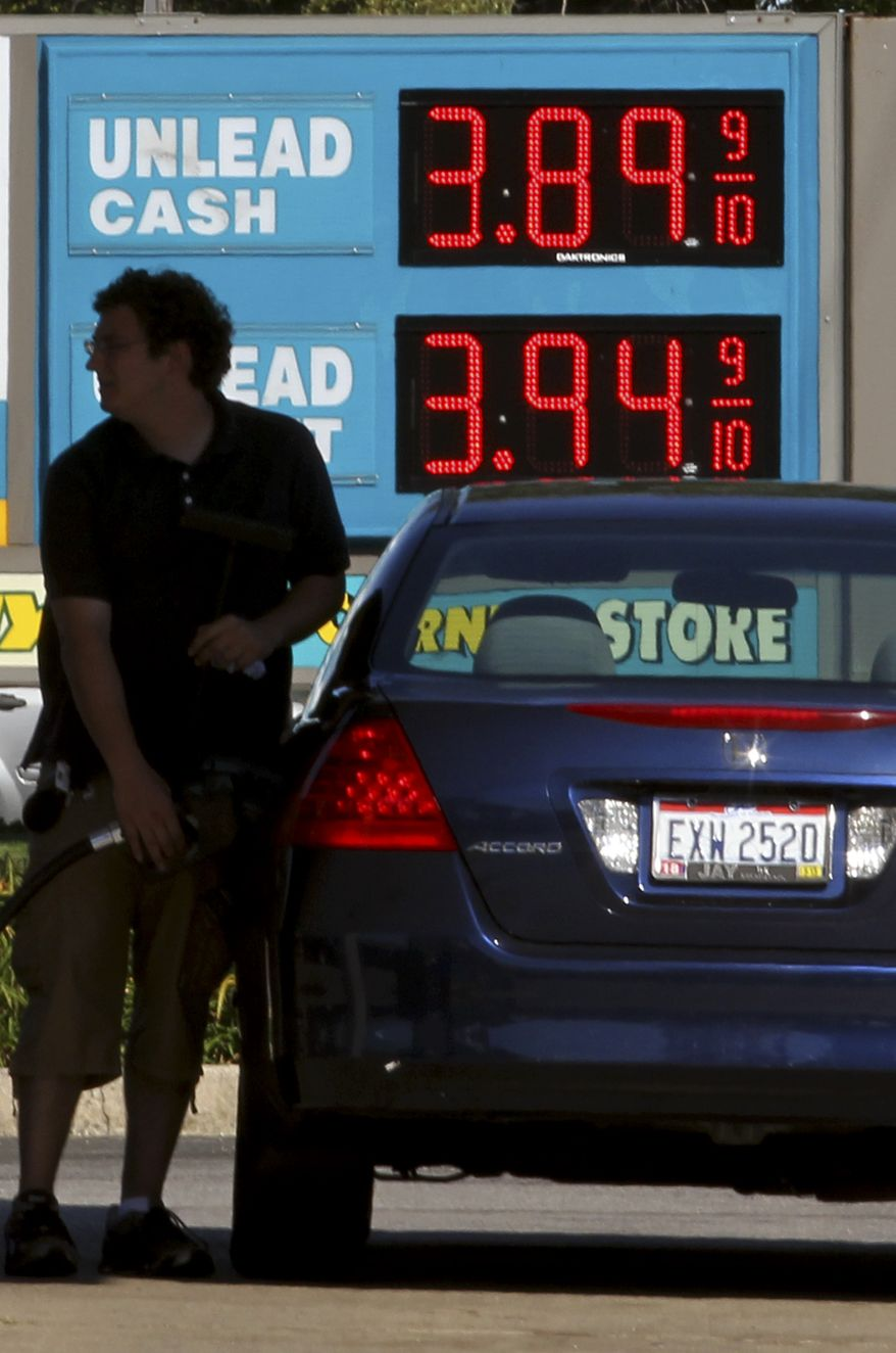 **FILE** A man fills his gas tank Aug. 29, 2012, at a gas station in Lyndhurst, Ohio. (Associated Press)