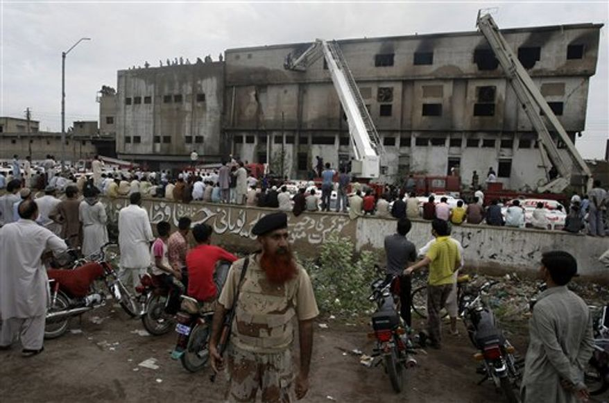 People gather at the site of burnt garment factory in Karachi, Pakistan, on Wednesday, Sept. 12, 2012. (AP Photo/Fareed Khan)