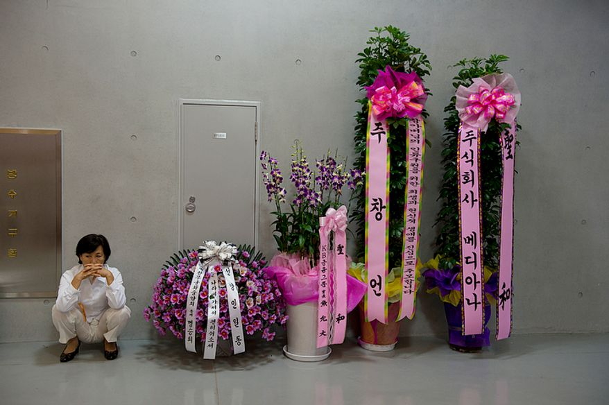 A mourner sits down near several flower arrangements at the Cheongpyeong Heaven and Earth Training Center complex near Seoul, Korea on Wednesday, Sept. 12, 2012. Although the announcement of the death of Unification Church founder Rev. Sun Myung Moon asked for no flowers, hundreds of these tribute flowers have poured into the complex over the last week.  (Barbara L. Salisbury/The Washington Times)
