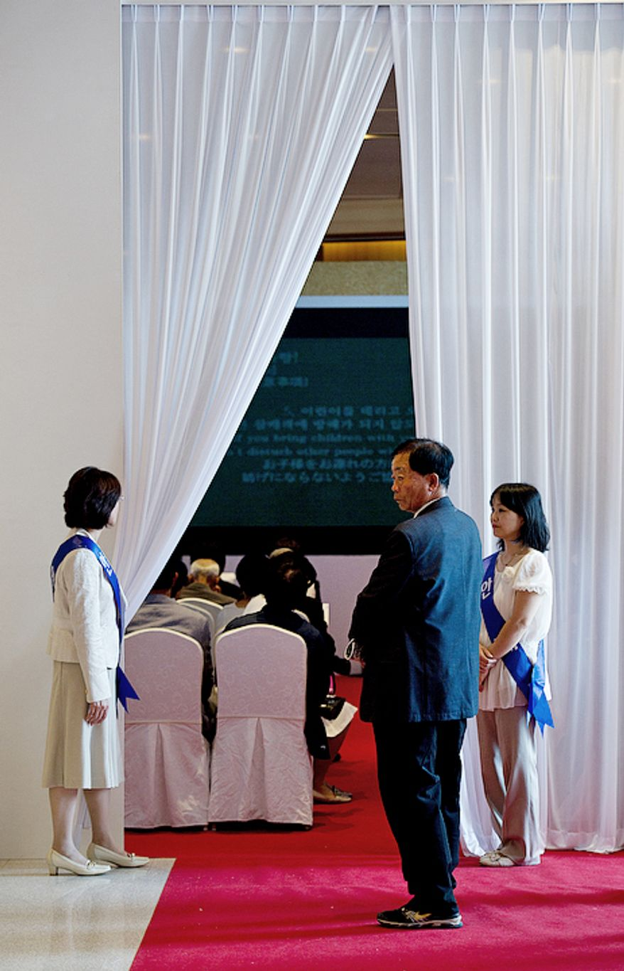 Ushers hold open a curtain that leads into a room to watch a video presentation on the life of the Rev. Sun Myung Moon inside the Cheongpyeong Heaven and Earth Training Center complex near Seoul, Korea on Wednesday, Sept. 12, 2012. Thousands of mourners have come over the past few days to pay tribute to the reverend. Once inside the complex, they first watched the video on his life, then signed in electronically before being given flowers to offer and the chance to write a remembrance on a special wall. (Barbara L. Salisbury/The Washington Times)
