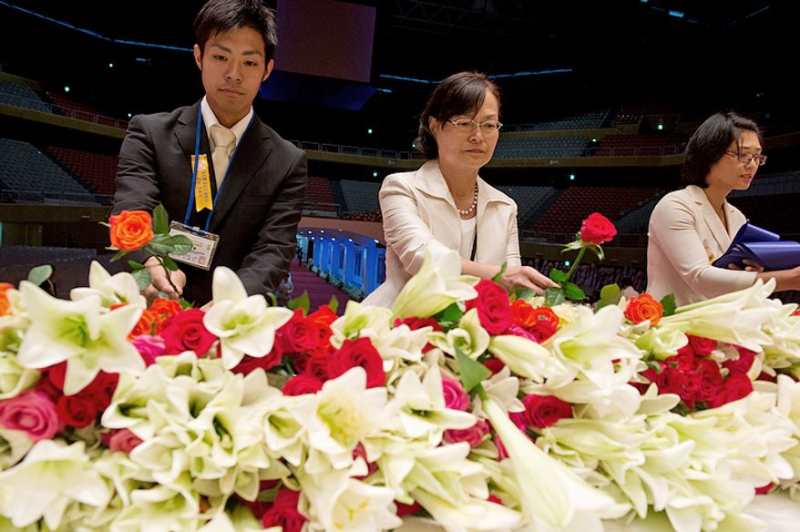 Mourners place flowers (lilies for the mother and roses for the father) on a table inside the Cheongpyeong Heaven and Earth Training Center near Seoul, Korea on Wednesday, Sept. 12, 2012 to honor the Rev. Sun Myung Moon, founder of the Unification Church. His 13-day funeral ends Saturday with a ceremony honoring his life followed by the burial. According to officials, they had to import flowers from Japan because they could not get enough in Korea. (Barbara L. Salisbury/The Washington Times)