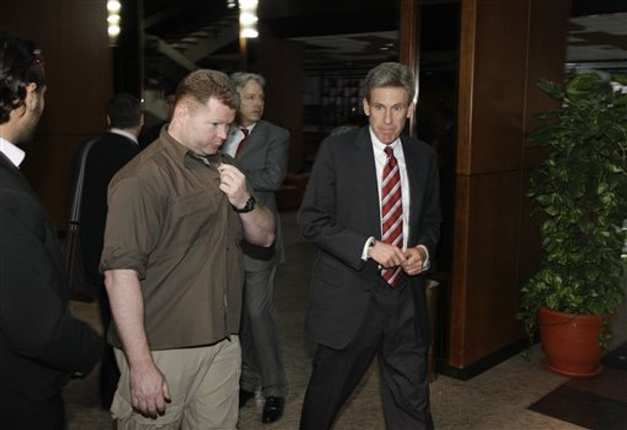 ** FILE ** In this photo taken Monday, April 11, 2011, then U.S. envoy Chris Stevens, right, is accompanied by an unidentified member of security personnel, left, as he attends meetings at the Tibesty Hotel where an African Union delegation was meeting with opposition leaders in Benghazi, Libya. (AP Photo/Ben Curtis)