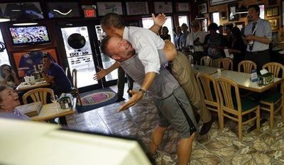 President Obama is picked-up and lifted off the ground by Scott Van Duzer, owner of Big Apple Pizza and Pasta Italian Restaurant, on Sept. 9, 2012, during an unannounced stop at the restaurant in Ft. Pierce, Fla. (Associated Press)