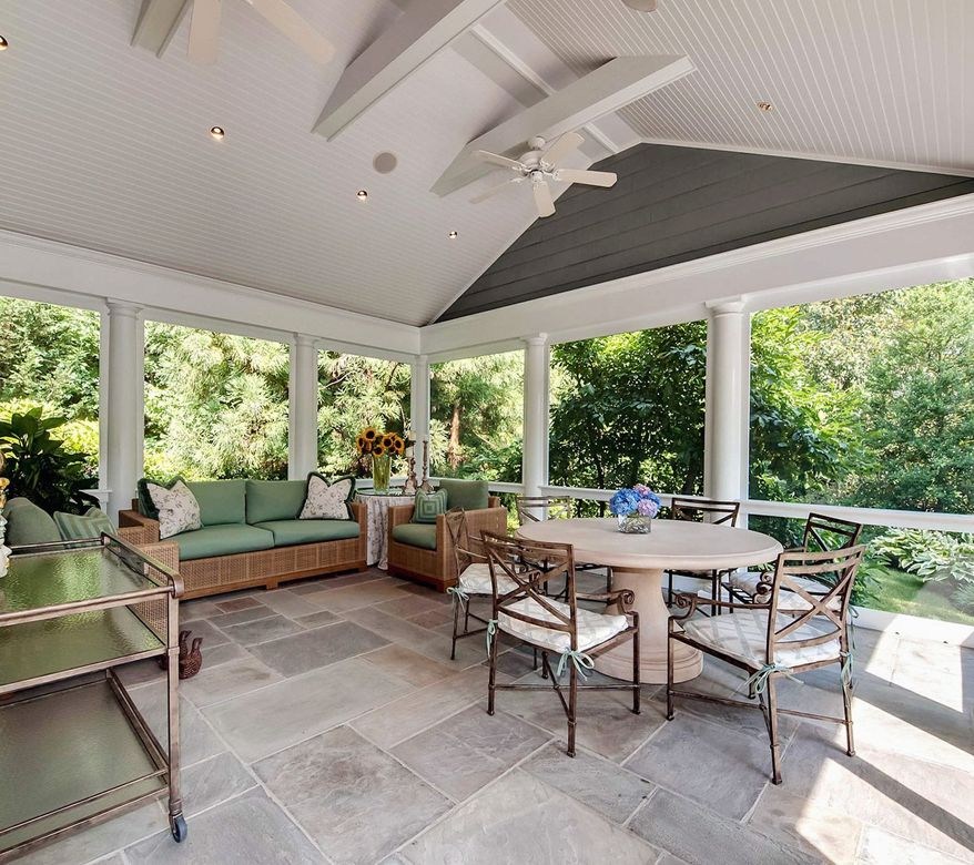 The screened-in rear porch has ceramic tile flooring, a vaulted ceiling and scenic views.