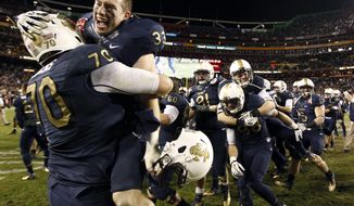 Navy offensive tackle Graham Vickers (70) and running back John Howell (33) celebrate on the field with their teammates after beating Army 27-21 in an NCAA college football game in Landover, Md., Saturday, Dec. 10, 2011. (AP Photo/Evan Vucci)