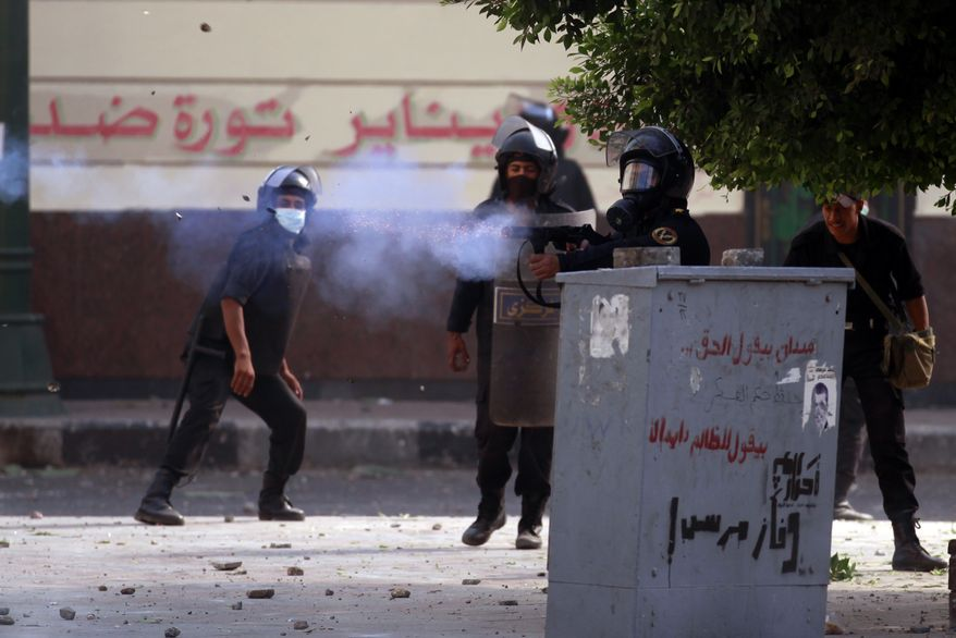 An Egyptian police officer shoots a tear gas canister toward protesters, unseen, during clashes near the U.S. embassy in Cairo, Egypt, Thursday, Sept. 13, 2012. Protesters clash with police near the U.S. Embassy in Cairo for the third day in a row. Egypt's Islamist President Mohammed Morsi vowed to protect foreign embassies in Cairo, where police were using tear gas to disperse protesters at the U.S. mission. (AP Photo/Khalil Hamra)