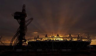 """** FILE ** In this March 5, 2012, file photo, the sun sets behind the main Olympic stadium and the """"Orbit"""" sculpture as seen from outside the London 2012 Olympic Aquatics Centre during the British Swimming Championship selection trials and Olympic test event at the Olympic Park in London. Senior lawmakers said Thursday, Sept. 13, 2012, that Britain's Houses of Parliament could temporarily leave its storied home to allow major repairs to take place — prompting calls for legislators to relocate to London's Olympic Park. (AP Photo/Matt Dunham, File)"""