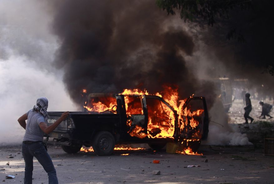 An Egyptian protester throws stones toward riot police next to a burning police car during clashes near the U.S. embassy in Cairo, Egypt, Thursday, Sept. 13, 2012. Protesters clash with police near the U.S. Embassy in Cairo for the third day in a row. Egypt's Islamist President Mohammed Morsi vowed to protect foreign embassies in Cairo, where police were using tear gas to disperse protesters at the U.S. mission. (AP Photo/Khalil Hamra)