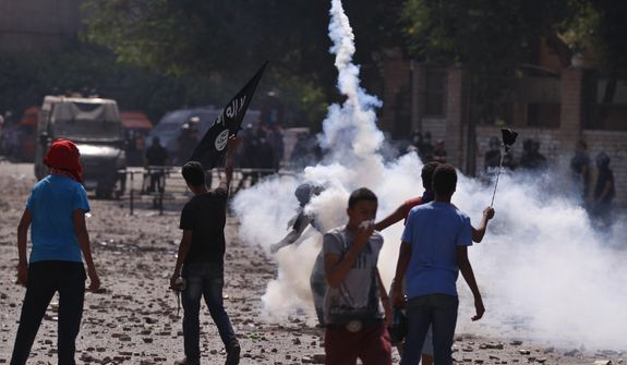 Egyptian protesters throw stones toward riot police, unseen, during clashes near the U.S. embassy in Cairo, Egypt, Thursday, Sept. 13, 2012. Protesters clash with police near the U.S. Embassy in Cairo for the third day in a row. Egypt's Islamist President Mohammed Morsi vowed to protect foreign embassies in Cairo, where police were using tear gas to disperse protesters at the U.S. mission. (AP Photo/Khalil Hamra)