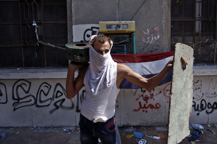 An Egyptian protester protects himself during clashes near the U.S. embassy in Cairo, Egypt, Thursday, Sept. 13, 2012. Protesters clash with police near the U.S. Embassy in Cairo for the third day in a row. Egypt's Islamist President Mohammed Morsi vowed to protect foreign embassies in Cairo, where police were using tear gas to disperse protesters at the U.S. mission. (AP Photo/Khalil Hamra)
