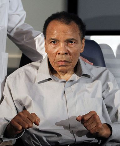 Former heavyweight boxing champion Muhammad Ali displays his signature fight pose after honoring outstanding surgeons and physicians at St. Joseph's Hospital's Barrow Neurological Institute in Phoenix on Wednesday, Feb. 22, 2012. (AP Photo/Ross D. Franklin)