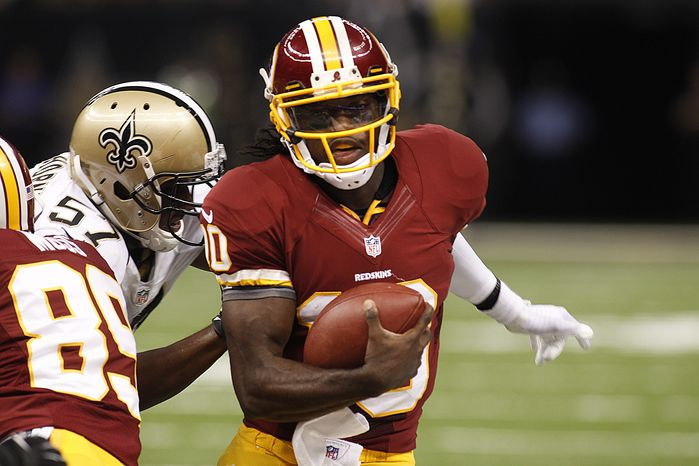 Washington Redskins quarterback Robert Griffin III (10) rushes past New Orleans Saints linebacker David Hawthorne (57) in the first half of an NFL football game against the New Orleans Saints at the Mercedes-Benz Superdome in New Orleans, Sunday, Sept. 9, 2012.  (AP Photo/Bill Haber)