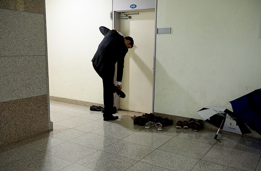 A man takes off his shoes before entering his makeshift dormitory in one of the seminary buildings at the Cheong Shim Peace World Center in Gapyeong-gun, Korea on Thursday, Sept. 13, 2012. Thousands of people are sleeping on the floor in various buildings throughout the complex to be here for the reverend's funeral, which takes place this Saturday. (Barbara L. Salisbury/The Washington Times)