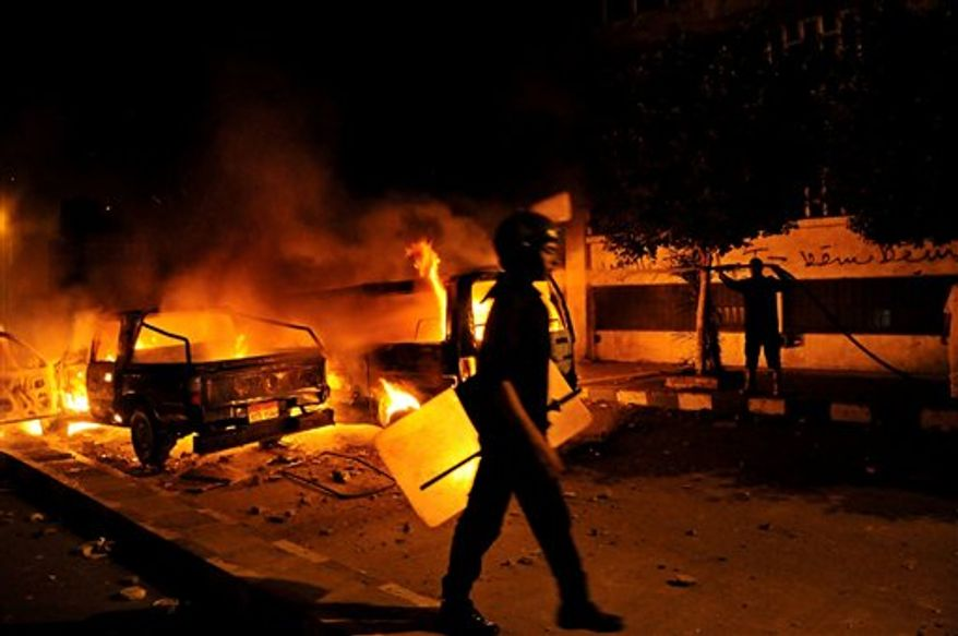 A riot policeman passes a burning vehicle during clashes outside the U.S. embassy in Cairo early Thursday, Sept. 13, 2012, as part of widespread anger across the Muslim world about a film ridiculing Islam's Prophet Muhammad. (Associated Press)