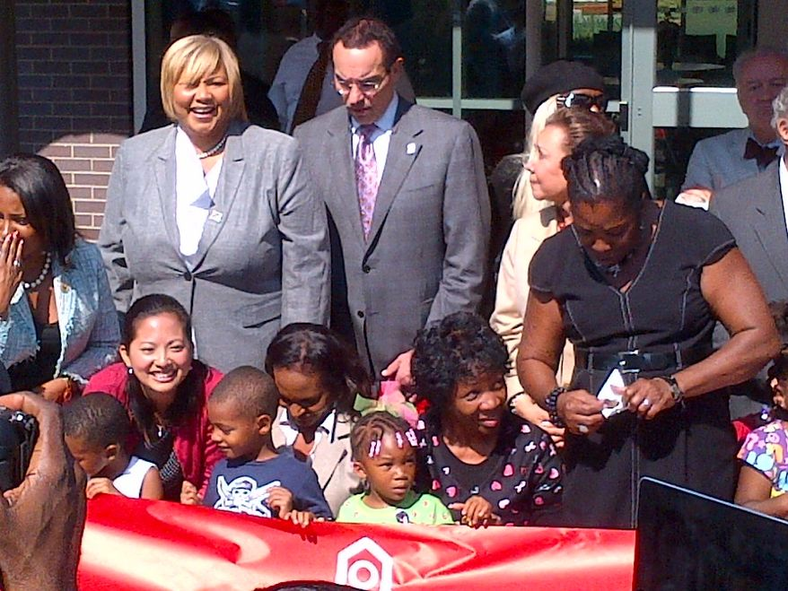 D.C. dignitaries joined city children on Thursday to cut the ribbon in front of Educare, a state-of-the-art center focusing on early childhood education in Ward 7. From left, are D.C. Housing Authority Director Adrianne Todman, council member Yvette M. Alexander, Ward 7 Democrat, and Mayor Vincent C. Gray. Dorothy Douglas, leaning over the banner in the black dress, is a member of the D.C. State Board of Education for Ward 7. (Tom Howell Jr./The Washington Times)