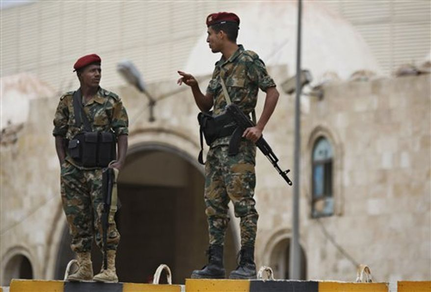 Yemeni soldiers stand guard in front of Yemen's President Abed Rabbu Mansour Hadi's house as protestors demonstrate to denounce terror attacks and hail the decisions by Hadi to replace security officials in Sanaa, Yemen, Wednesday, Sept. 12, 2012. Yemen's defense minister narrowly escaped assassination Tuesday when a powerful car bomb ripped through his motorcade as it traveled in the nation's capital, killing at least 13 people in an attack that bore the hallmarks of al Qaeda. (AP Photo/Hani Mohammed)