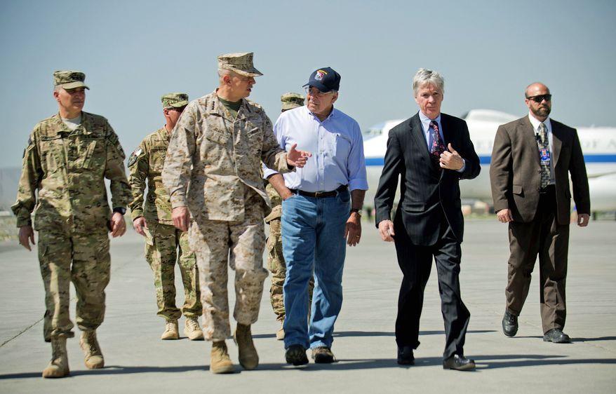 **FILE** U.S. Defense Secretary Leon Panetta (center) speaks June 7, 2012, with Ryan Crocker, U.S. Ambassador to Afghanistan, and Gen. John Allen (left center), the head of NATO coalition forces in Afghanistan, upon arriving at Kabul International Airport in Kabul, Afghanistan. (Associated Press)