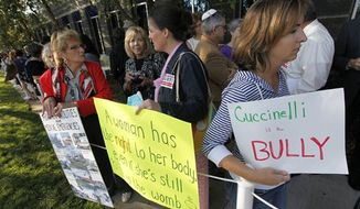 Protesters hold signs as they wait for the Virginia Board of Health meeting on abortion clinic regulations in Richmond, Va., Friday, Sept. 14, 2012. Activists on both sides of the abortion issue have gathered outside the meeting and the board was scheduled to take comments before voting on the regulations Friday. (AP Photo/Steve Helber)