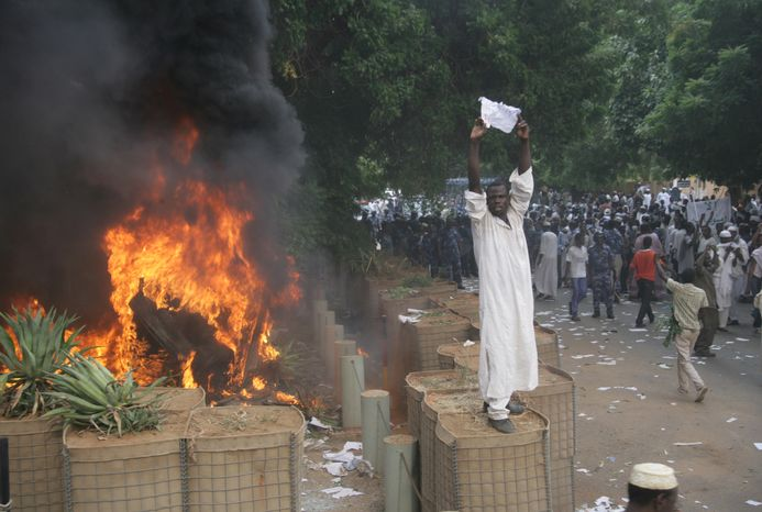 A Sudanese protester stands on a barricade during a demonstration in Khartoum, Sudan, on Sept. 14, 2012, as anger continued to spread across the Muslim world about a film ridiculing Islam's Prophet Muhammad. Germany's Foreign Minister said the country's embassy in Khartoum has been stormed by protesters and set partially on fire. (Associated Press)