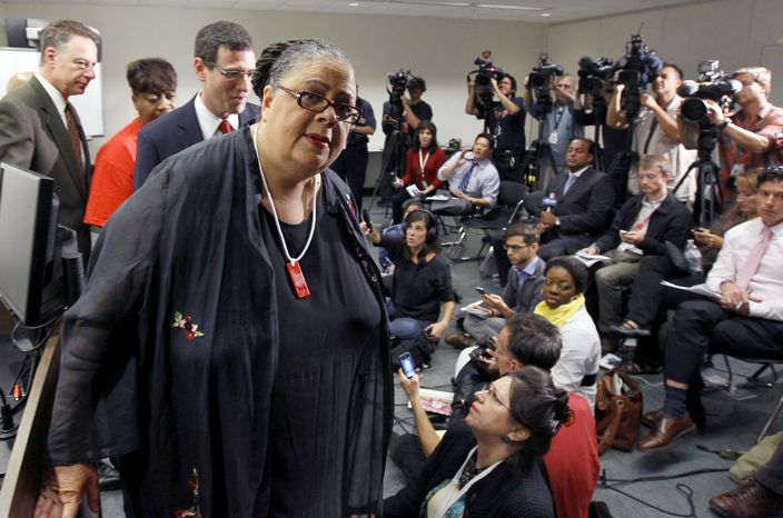 """Karen Lewis, president of the Chicago teachers union, departs a news conference after her meeting with the union's House of Delegates Friday, Sept. 14, 2012, in Chicago. Lewis told the delegates that a """"framework"""" was in place to end the teachers strike. (AP Photo/Charles Rex Arbogast)"""