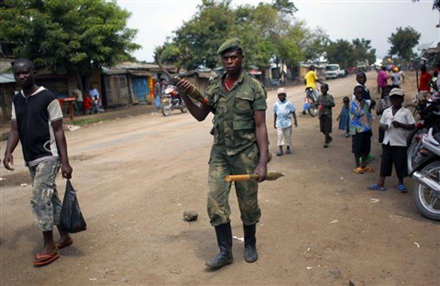 ** FILE ** In this Aug. 5, 2012, file photo, an M23 rebel walks the streets of the North Kivu town of Rubare near Rutshuru, 75 km (48 miles) North of Goma, Congo. (AP Photo/Jerome Delay, File)