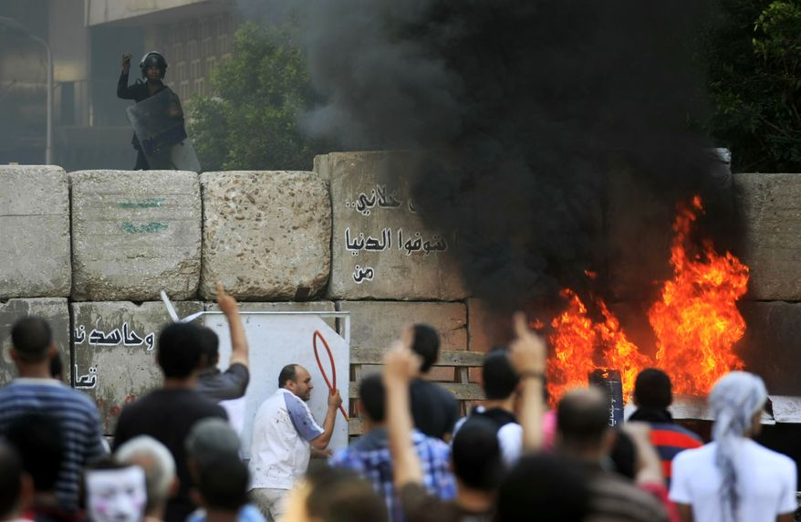 Egyptian protesters clash with security forces near the U.S. embassy in Cairo, Egypt, Friday, Sept. 14, 2012, as part of widespread anger across the Muslim world about a film ridiculing Islam's Prophet Muhammad. (AP Photo/Khalil Hamra)