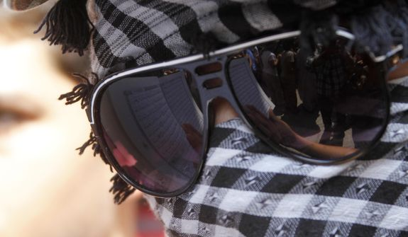 A protester reads the Quran, Muslims' holy book, reflected in his sunglasses, during a protest about a film ridiculing Islam's Prophet Muhammad in the Palestinian refugee camp of Ain el-Hilweh near Sidon, Lebanon, Friday, Sept. 14, 2012. (AP Photo/Mohammed Zaatari)